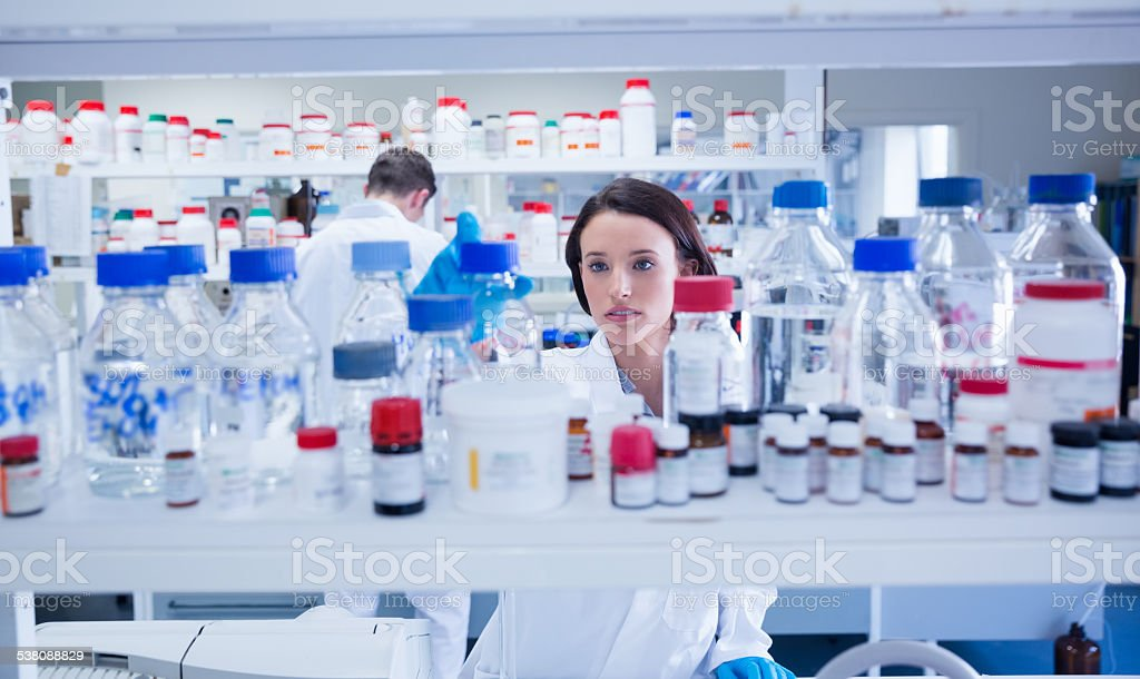 Young chemist picking up bottles on shelf stock photo