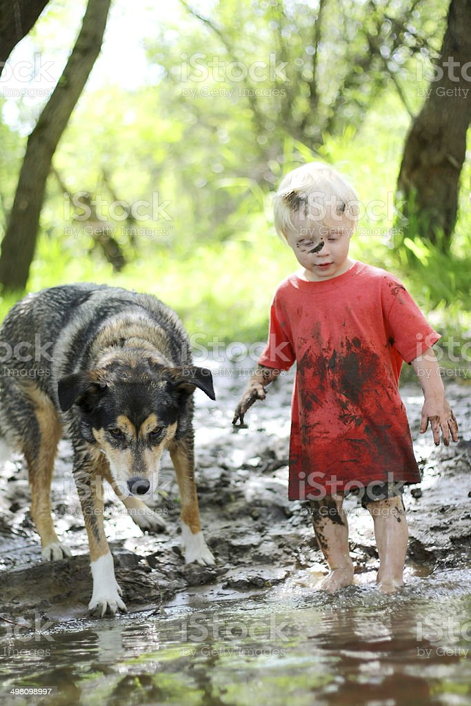 Young Child and Dog Playing in Muddy River stock photo