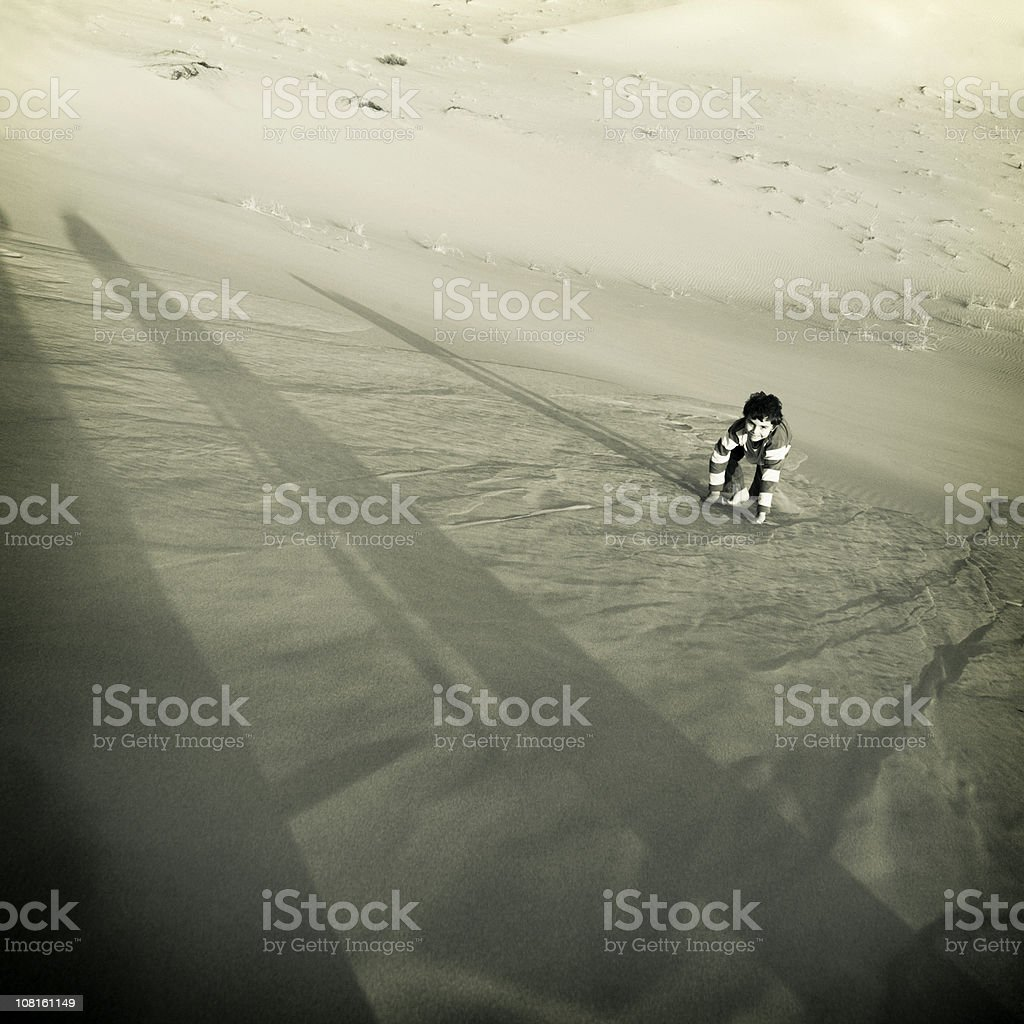 Young Child Climbing Up Steep Sand Dune stock photo