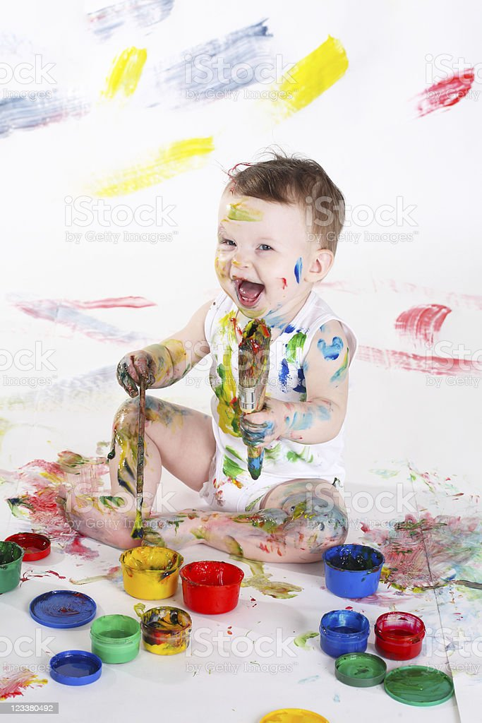 Young child covered in colorful paint and making mess royalty-free stock photo