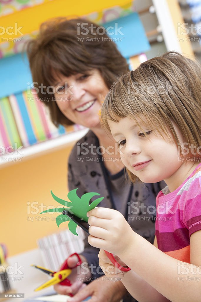 Young child doing crafts with her grandmother royalty-free stock photo