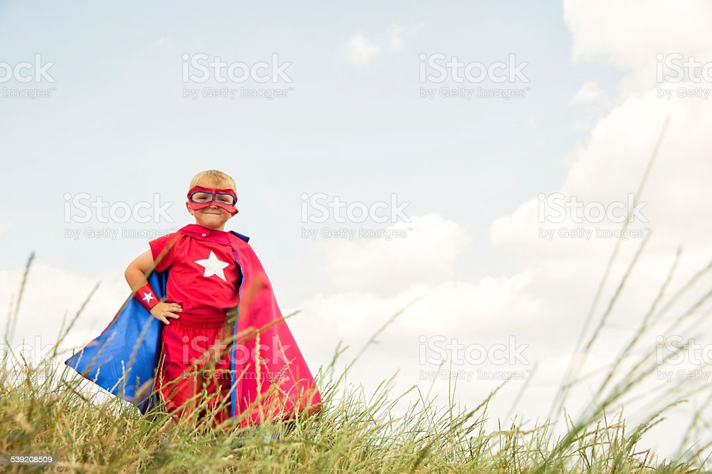 Young Child Dressed as Superhero in Tall Grass stock photo