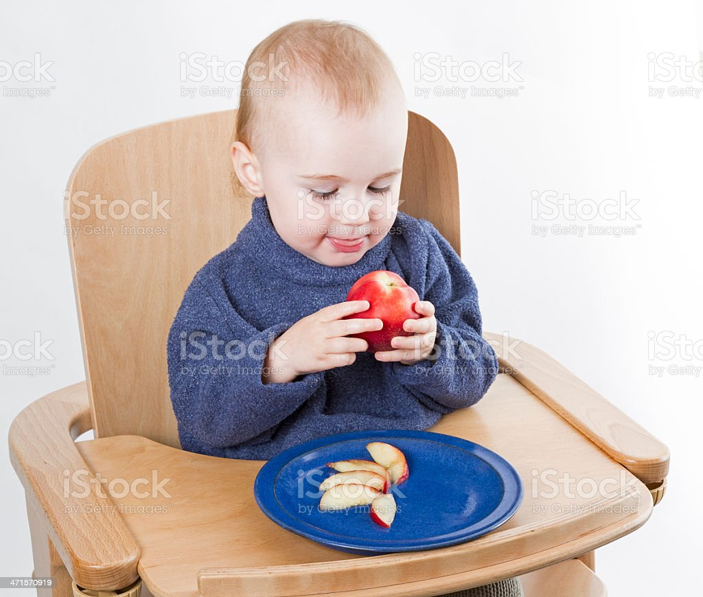 young child eating peaches in high chair stock photo
