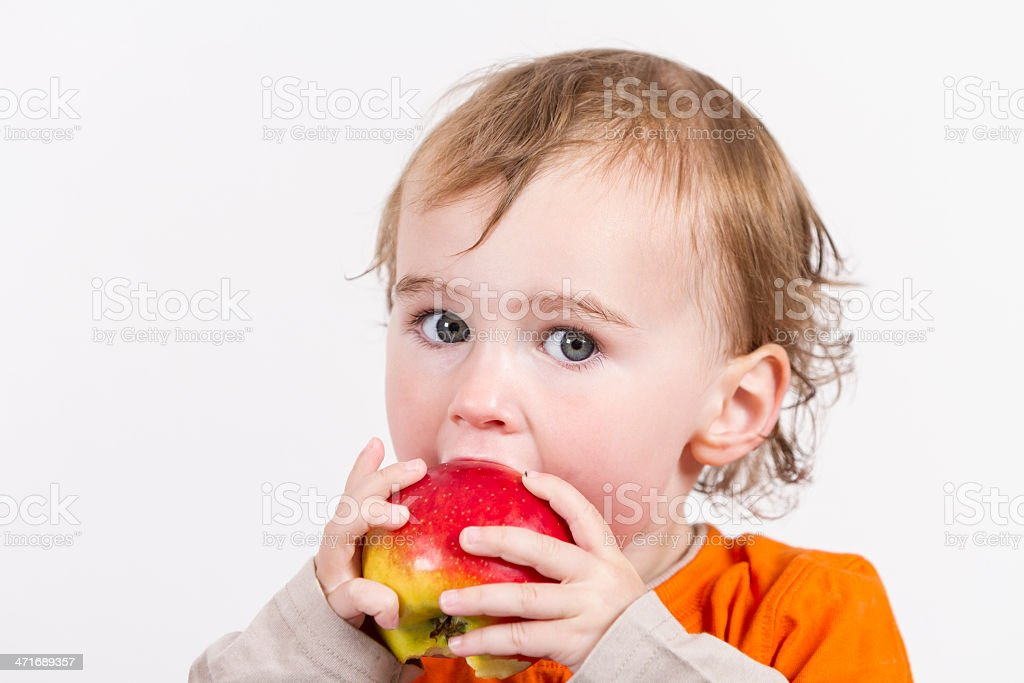 young child eating red apple stock photo