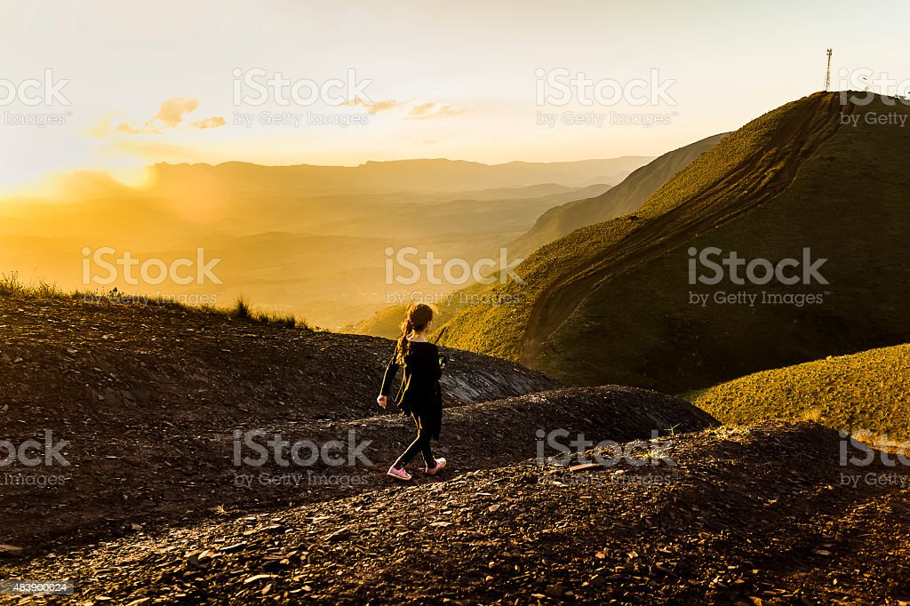 Young Child Hiking on Top of Mountain at Sunset stock photo