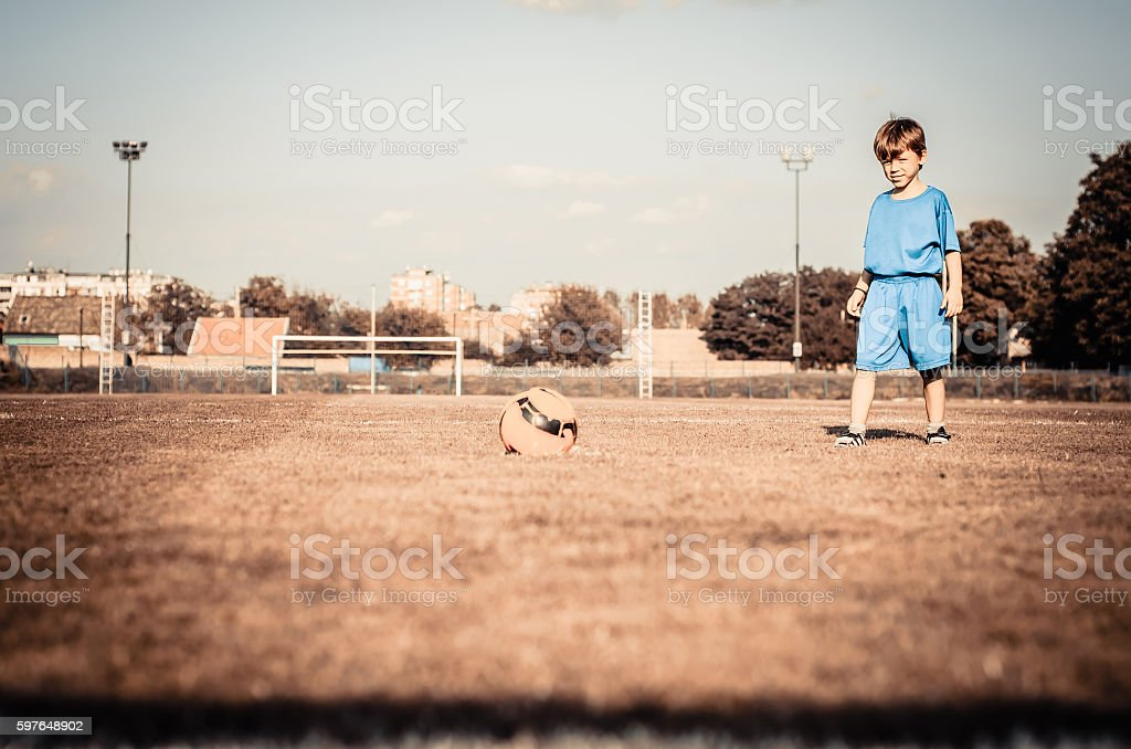Young child hits the ball on the soccer field stock photo