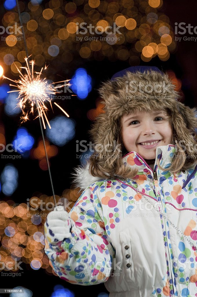 Young child in coat and hat holding a sparkler royalty-free stock photo