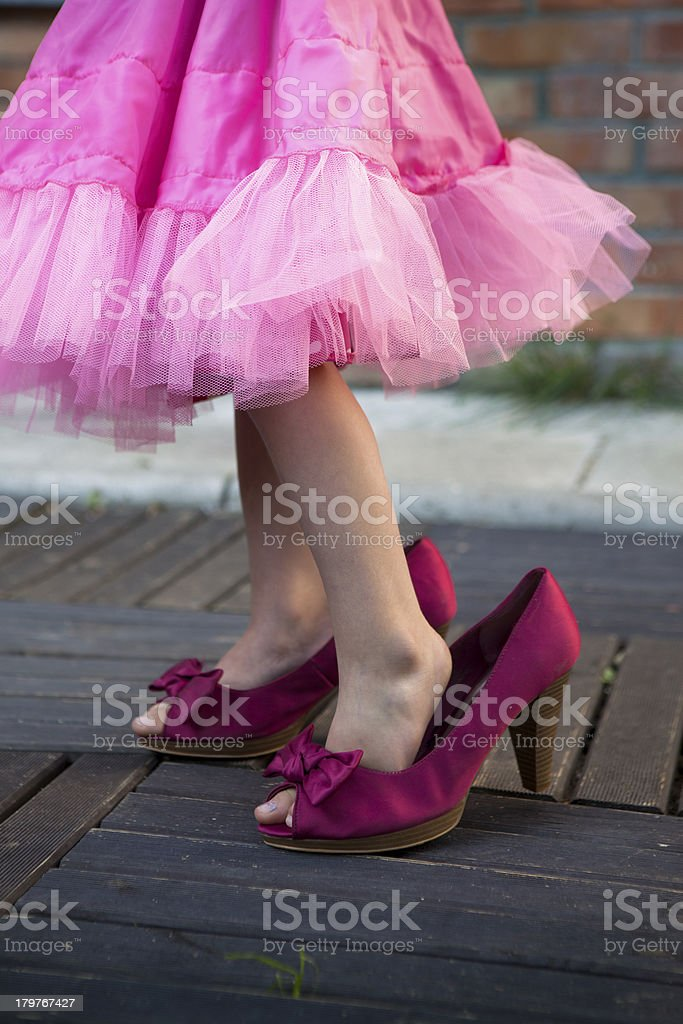 Young child in pink dress in mother's high heel pink shoes royalty-free stock photo