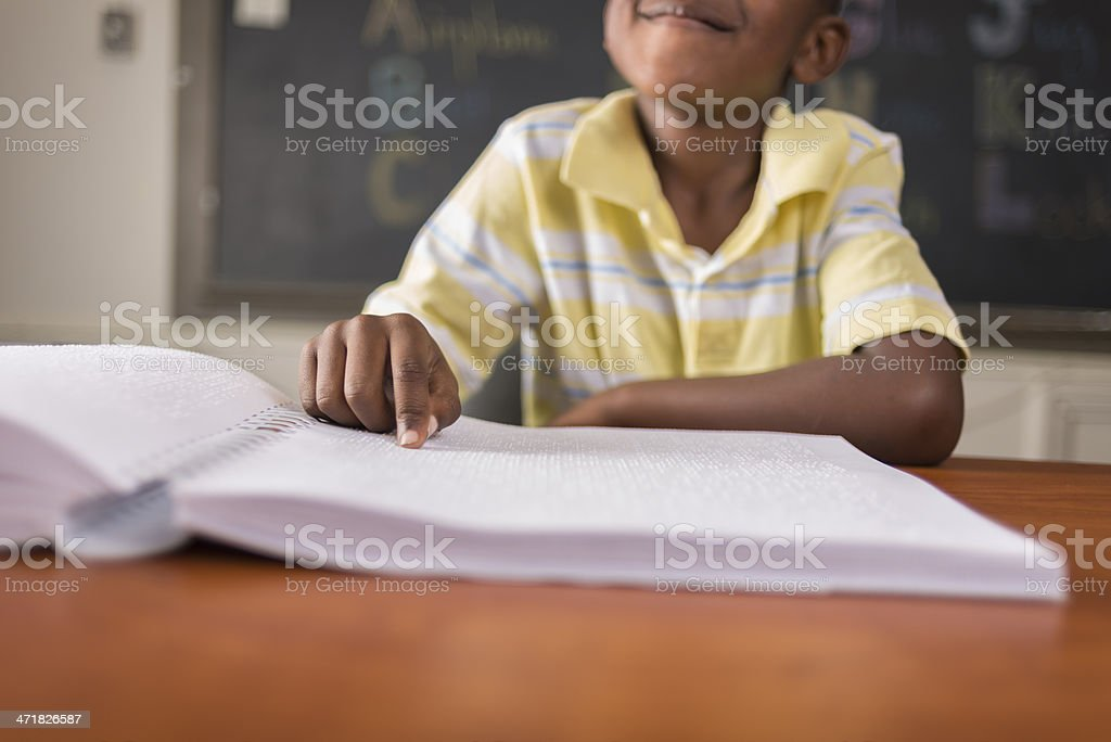 Young child learning Braille in classroom royalty-free stock photo