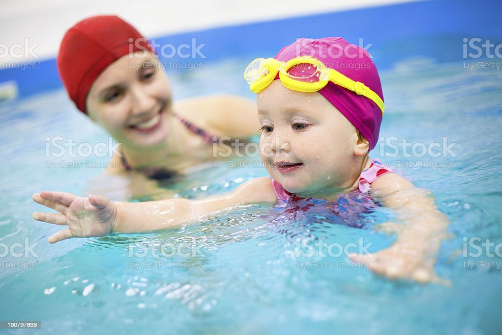 Young Child Learning How to Swim with an Adult stock photo