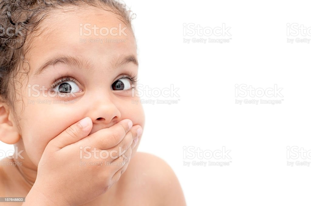 Young child looking surprised and covering mouth with hand stock photo