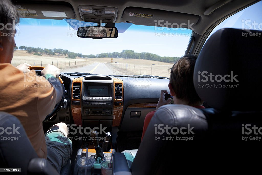 Young child on a portable device while father drives an SUV stock photo