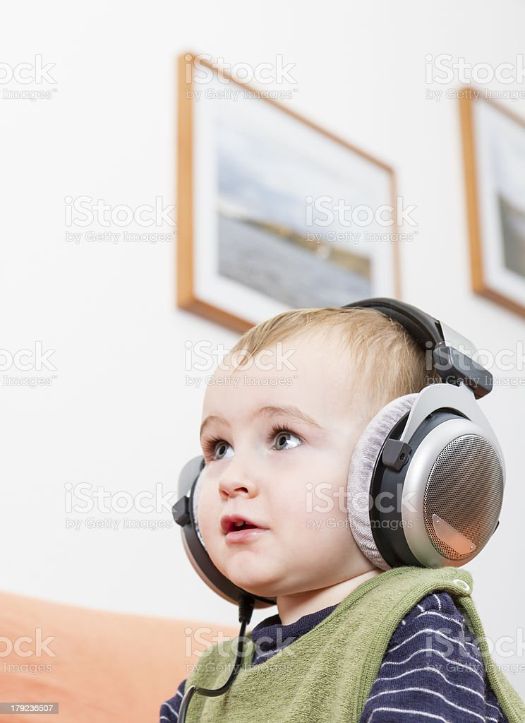 young child on couch with headphone stock photo