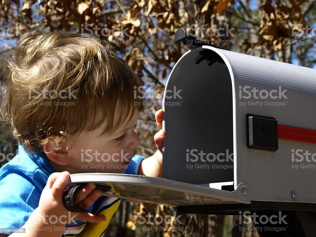 A young child opens a mailbox to check what is inside stock photo