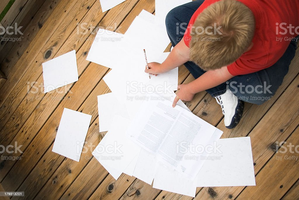 Young child sat on a wooden floor writing his homework royalty-free stock photo