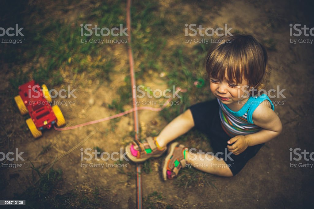 Young child sitting on the ground stock photo