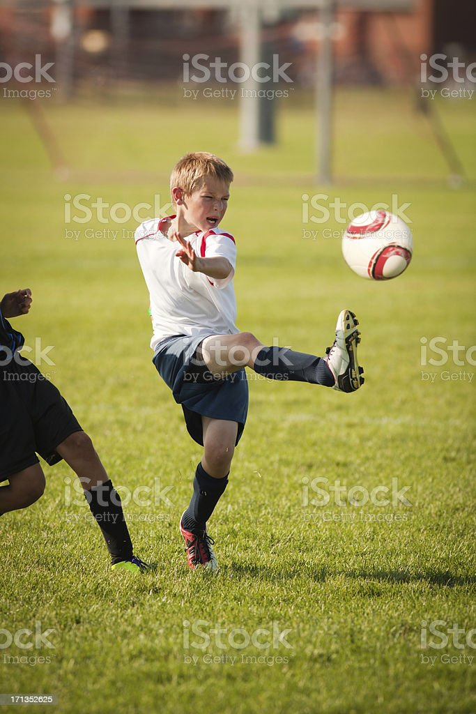 Young Child Soccer Player in Game Action stock photo