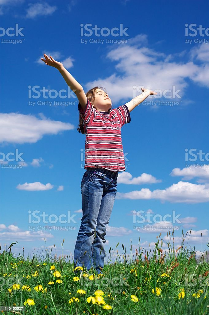 Young child standing in a field lifting arms toward the sky royalty-free stock photo