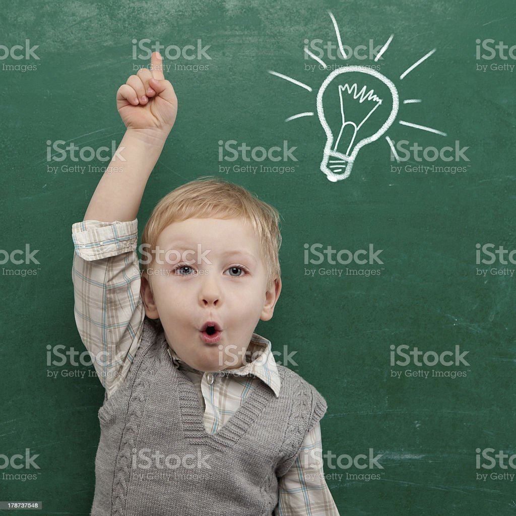 Cheerful smiling child at the blackboard. School concept