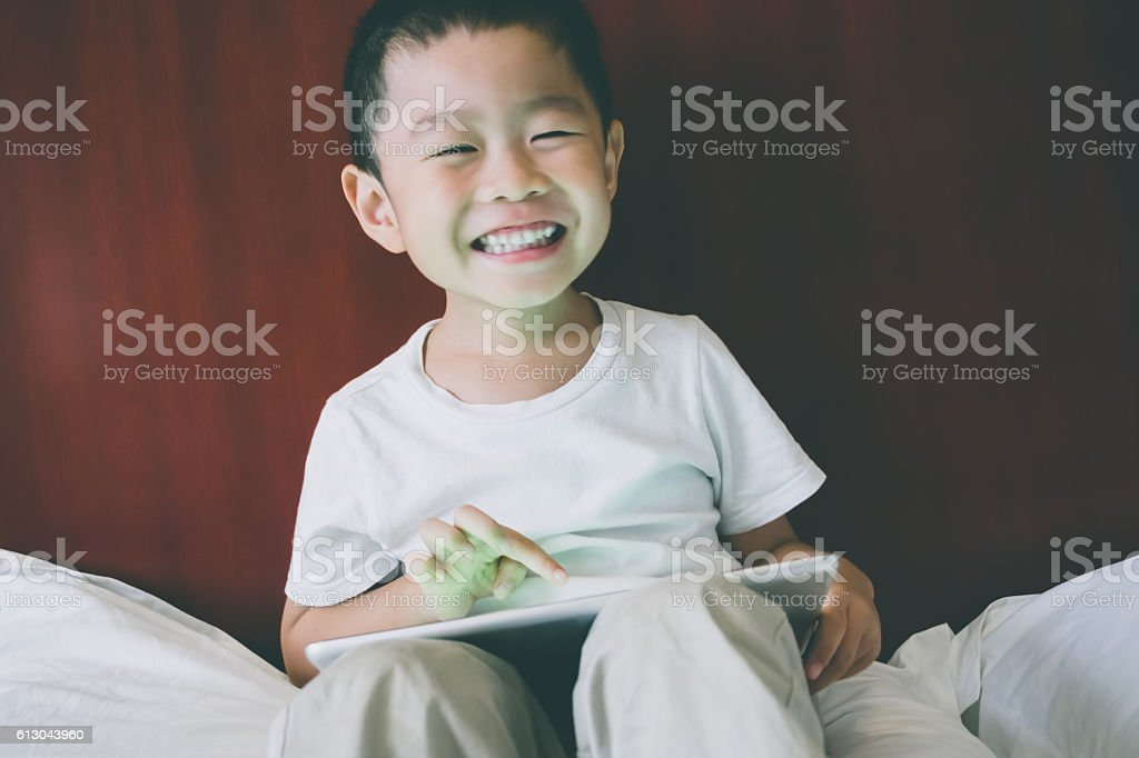 Young child using digital tablet in bed stock photo