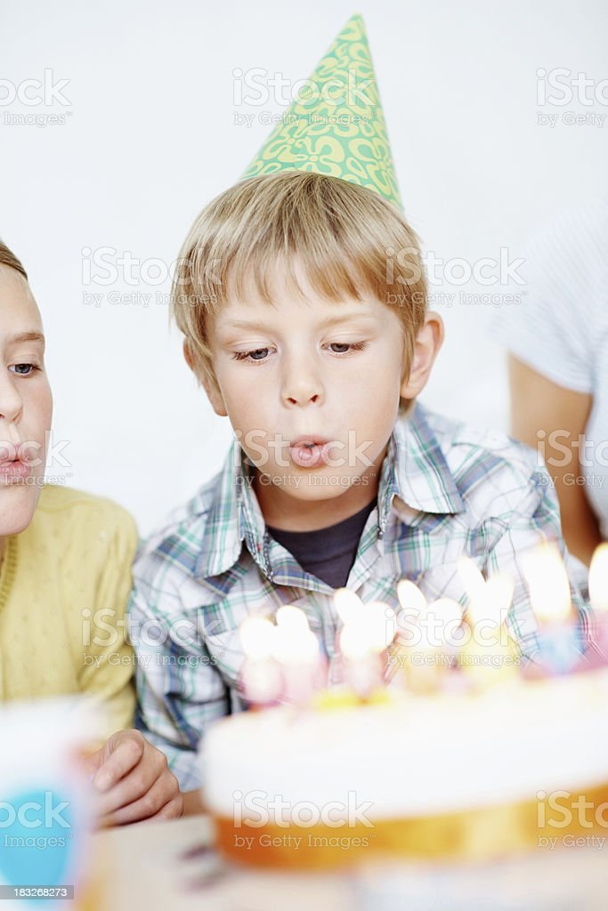 Young child wearing party hat and blowing birthday candles royalty-free stock photo