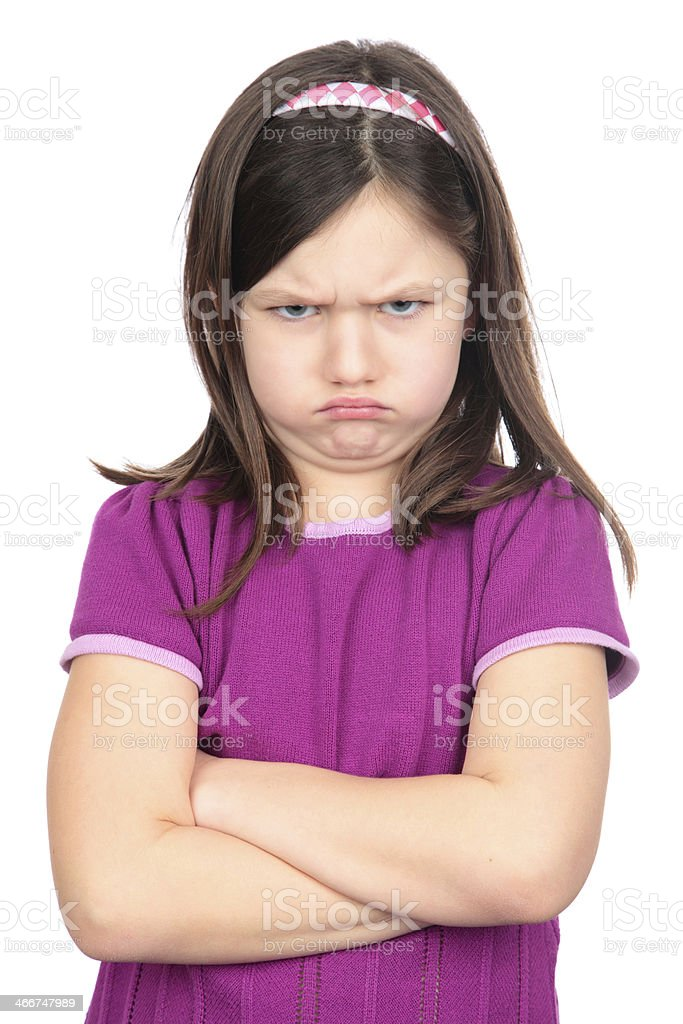 A young child with a grumpy face. stock photo