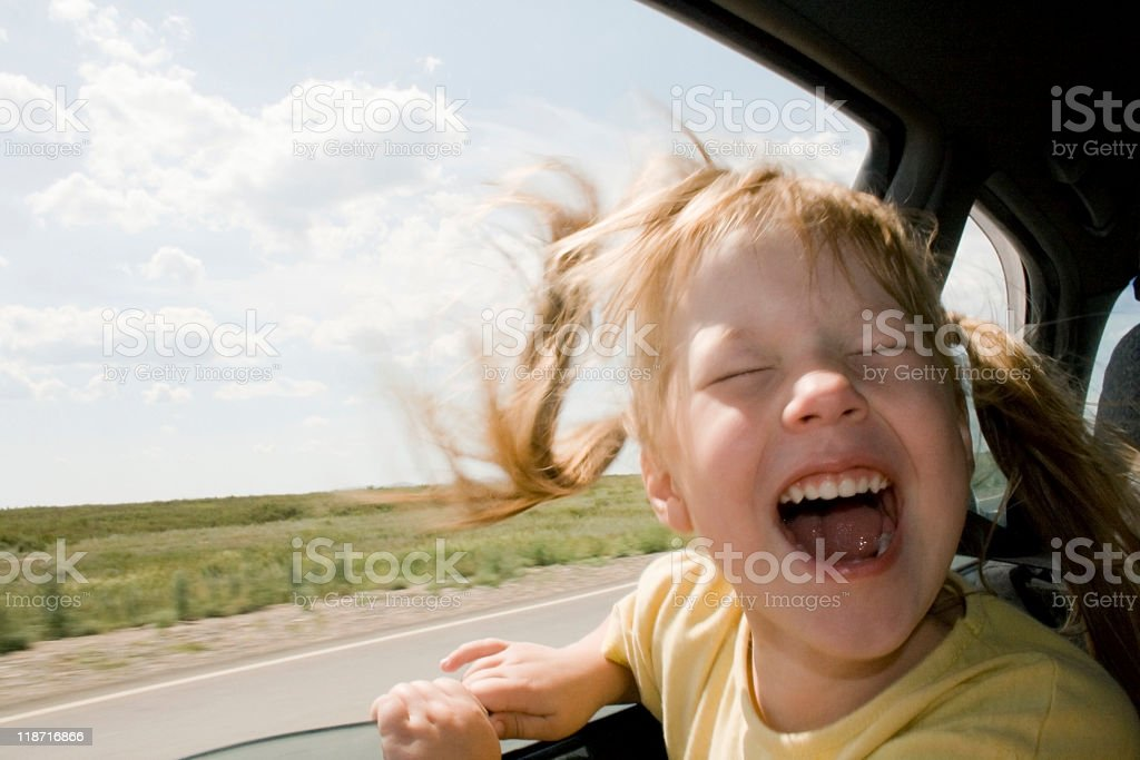 Young child with the wind on her face in the car stock photo