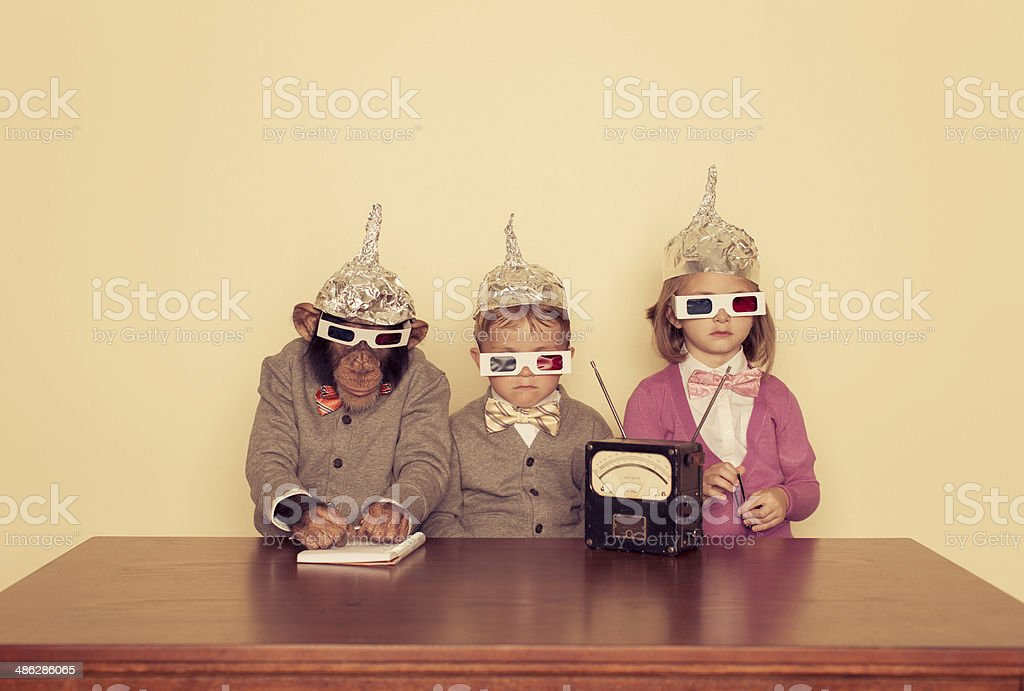 Young Children and Chimpanzee Wear Tinfoil Hats stock photo