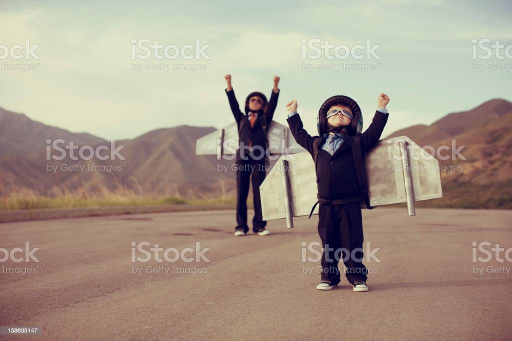 Young Children Dressed in Business Suits and Jetpacks stock photo