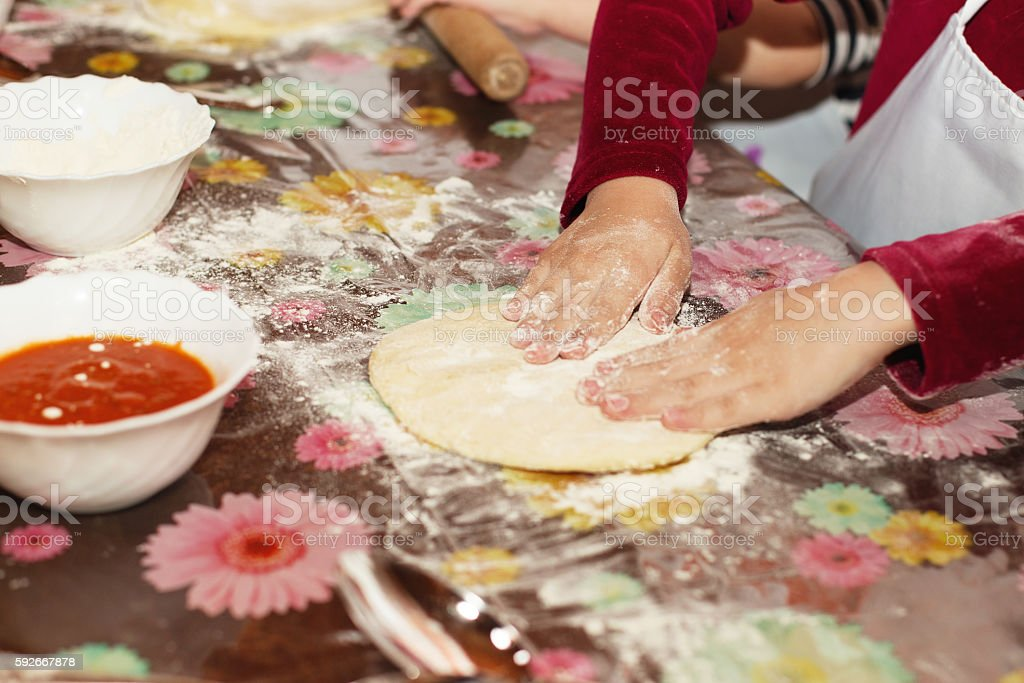 Young children learn to cook a pizza. stock photo
