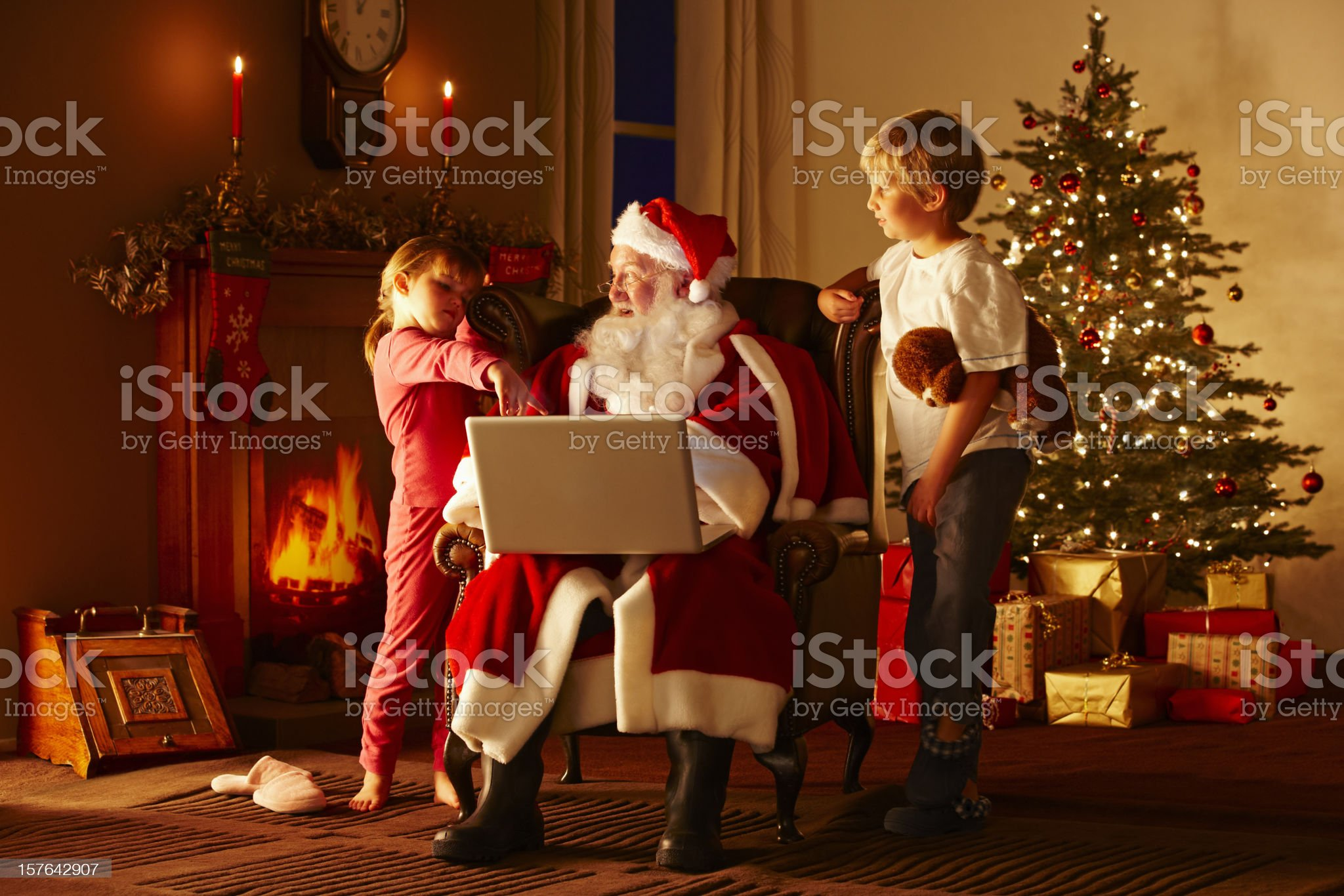 Young children looking at a laptop with Santa Claus royalty-free stock photo