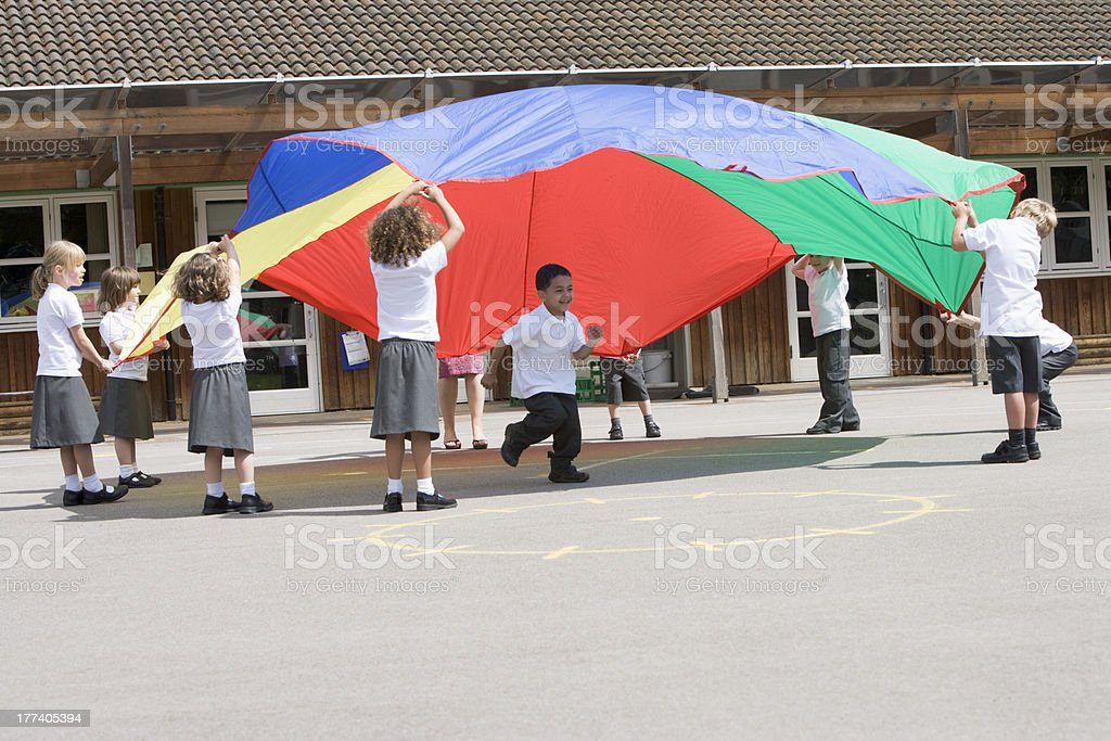 Young children playing with a parachute in the playground stock photo