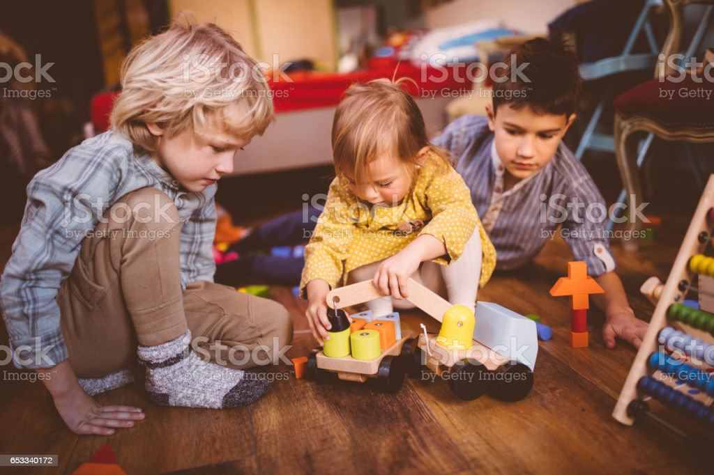 Young children playing with toys on bedroom floor stock photo