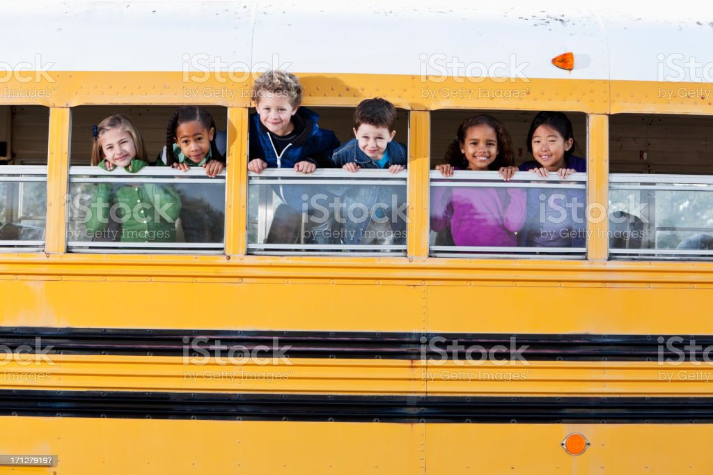 Young children poking heads out school bus windows stock photo