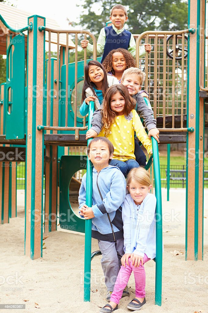 Young Children Sitting On Climbing Frame In Playground stock photo