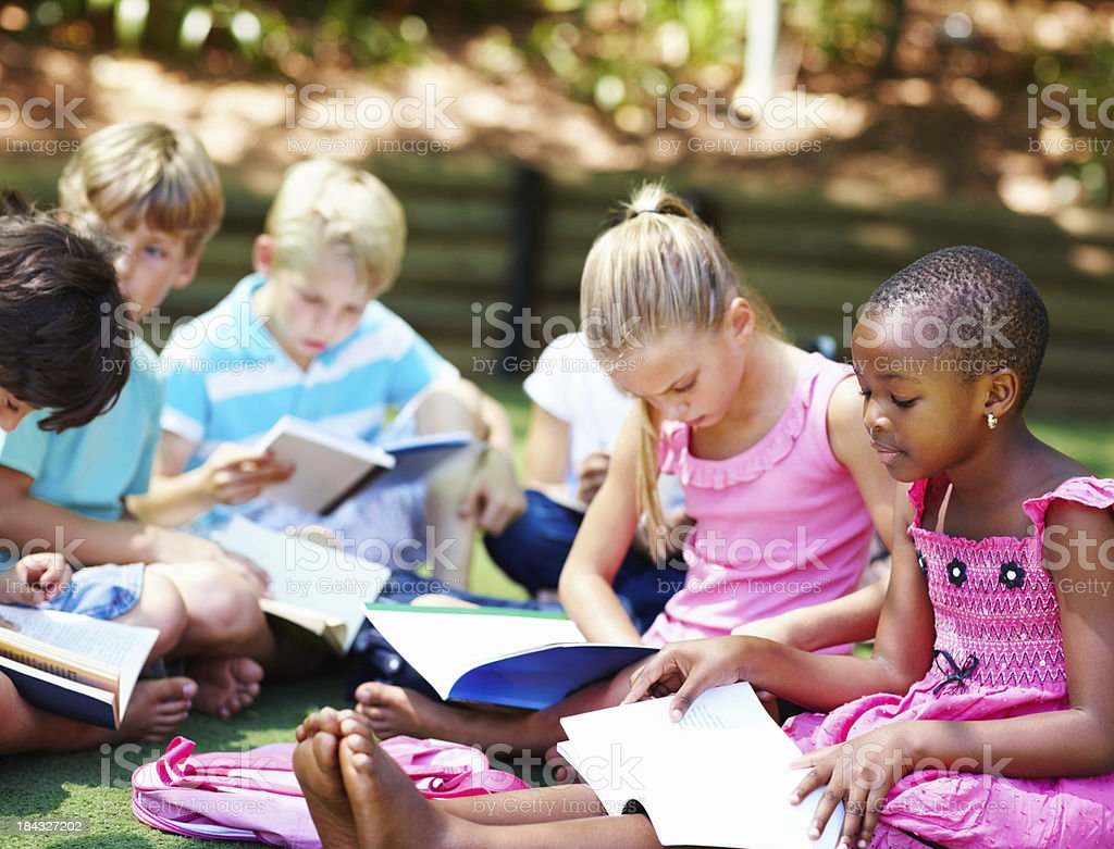 Young children sitting on grass and studying stock photo