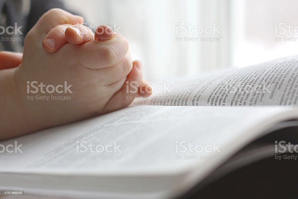 Young Child's Hands Praying on Holy Bible stock photo
