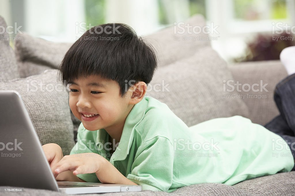 Young Chinese Boy Using Laptop Relaxing On Sofa At Home royalty-free stock photo