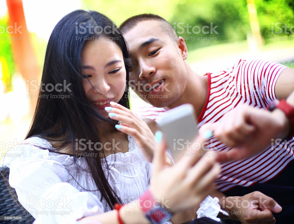 Young Chinese couple taking selfie. stock photo
