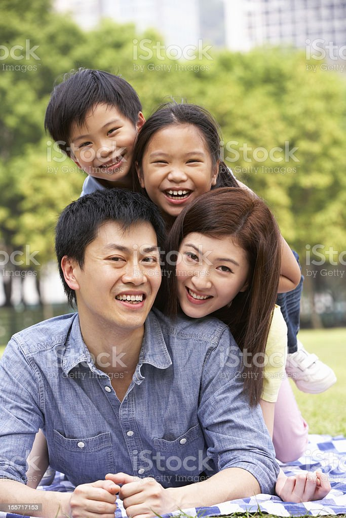 Young Chinese Family Relaxing In Park Together royalty-free stock photo