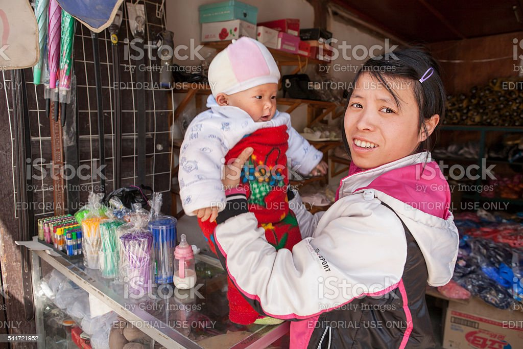 Young Chinese girl  tradeswoman holding a baby on the hands. stock photo