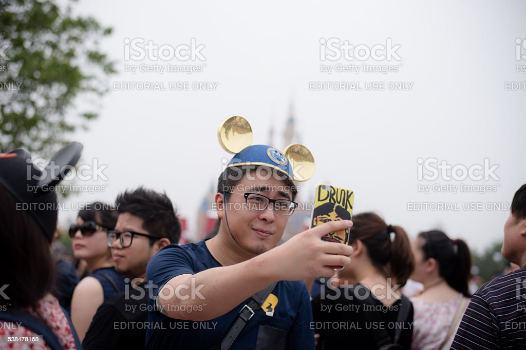 Young chinese man taking a Selfie in Shanghai, Disneyland stock photo