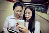 Young Chinese woman checking mobile phone together