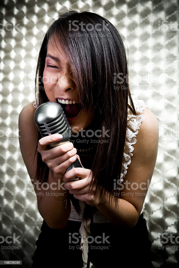 Young Chinese Woman Singing into Microphone royalty-free stock photo