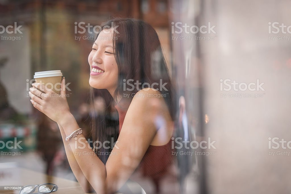 young chinese woman sitting next to windows in cafe. stock photo