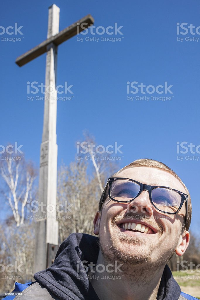 Young christian in glasses smiling under a cross royalty-free stock photo