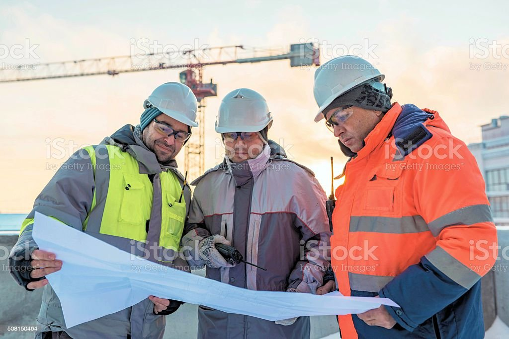 Young Civil Engineers and Senior Foreman At Construction Site stock photo
