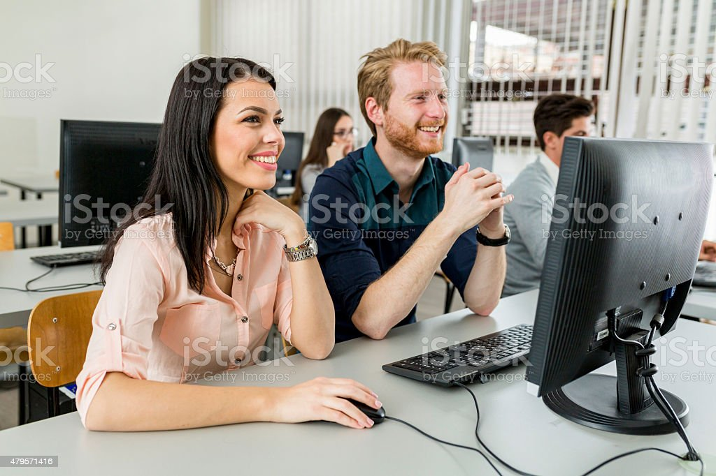 Young classmates looking at a monitor and studying stock photo