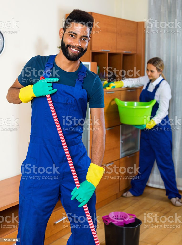 Young cleaners cleaning and dusting in house stock photo