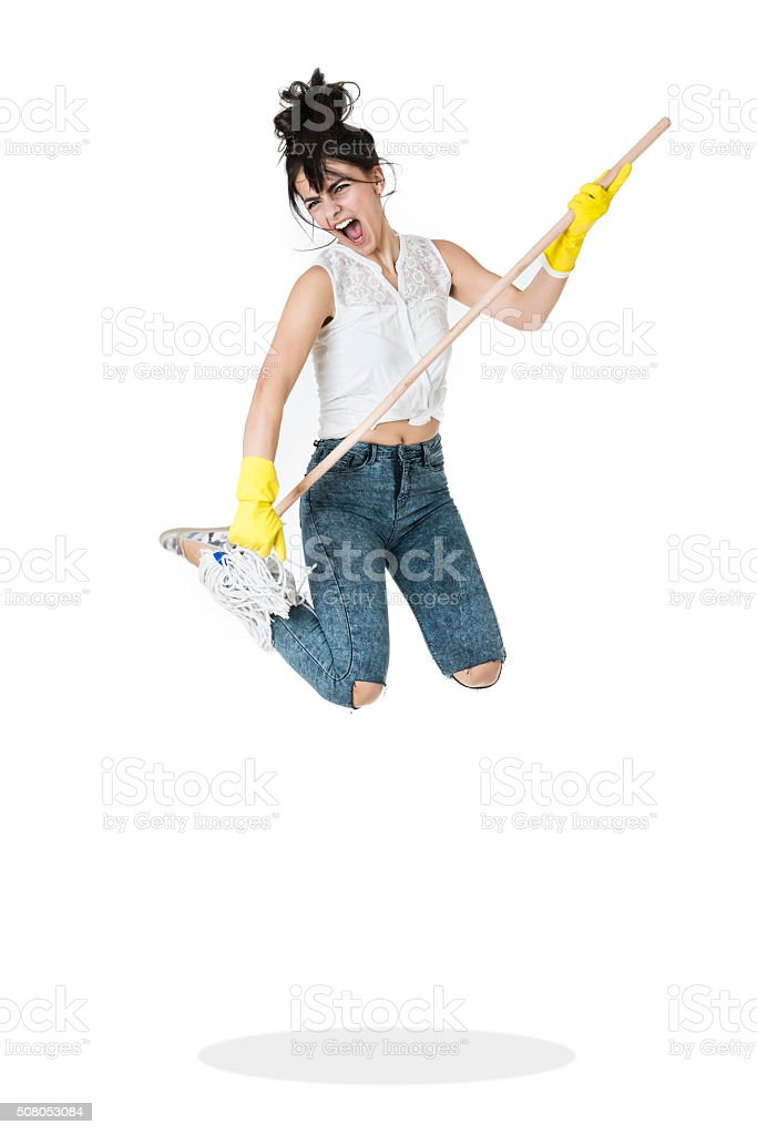 Young Cleaning Housewife Jumping and Playing Guitar with the Broom stock photo